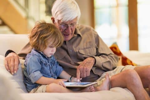 Caucasian grandfather and grandson using digital tablet